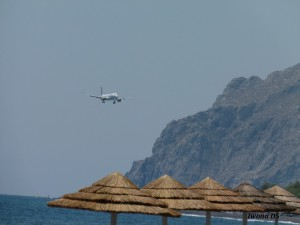 kamari czarna plaża,przelatujący samolot